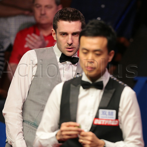 30.04.2016. The Crucible, Sheffield, England. World Snooker Championship. Semi Final, Mark Selby versus Marco Fu. Mark Selby looks on at his snooker, as Marco Fu chalks up