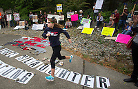 "Gina Nunez, 11, from Buckley, Wash. leaps over a banner that says ""Stop the Slaughter"" on her way to address the crowd protesting the killing of the Profanity Peak wolf pack outside the Washington Department of Fish and Wildlife (WDFW) headquarters in Olympia, Washington on September 1, 2016.""There shouldn't be a reason to kill wolves if there's more cows than wolves in Washington."" she said. Nunez was there with her mother Jill Nunez. ""It's our first protest,"" said Jill. ""We felt so strongly about this."" (photo © Karen Ducey Photography)"