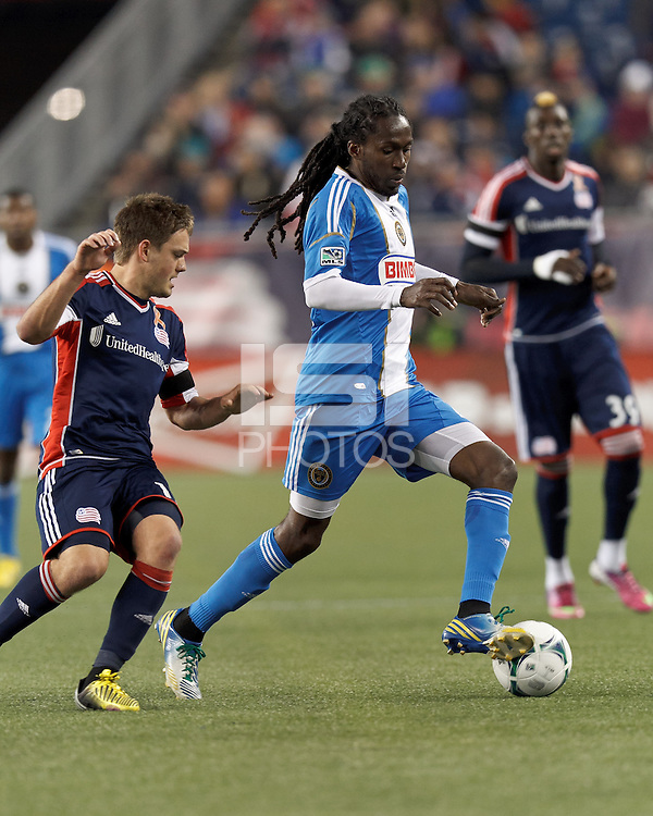 Philadelphia Union midfielder Keon Daniel (26) dribbles as New England Revolution midfielder Kelyn Rowe (11) pressures.In a Major League Soccer (MLS) match, the New England Revolution (blue/red) defeated Philadelphia Union (blue/white), 2-0, at Gillette Stadium on April 27, 2013.