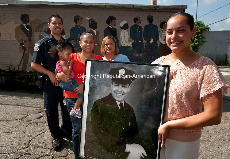 "WATERBURY, CT-03 AUGUST 2012--080312JS01- Jessica Rivera, right, holds a photo of her late father Heriberto T. Rivera as friend Waterbury police officer Matthew Ocasio, niece Andrea Camerl, 2, sister Martiza Rivera and mother Martiza Rivera (same names), pose for a photograph outside the Rivera Memorial Foundation on Cherry Street in Waterbury on Thursday. The family is preparing for the Rivera & Hughes Community Family Day Saturday at Library Park in Waterbury. The event is in memory of  former Waterbury firefighter Heriberto ""Eddie"" T. Rivera..Jim Shannon Republican-American"