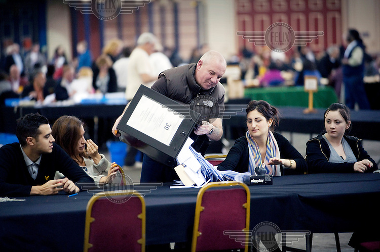 Ballot papers being emptied from a ballot box at the vote count in the Great Hall at Alexandra Palace in North London...