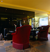 Armchairs covered in rich red velvet furnish the hotel lobby