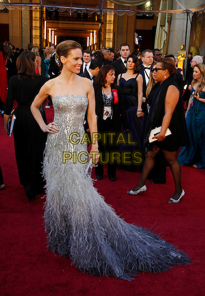 HILARY SWANK.83rd Annual Academy Awards - Oscars.Kodak Theatre, Hollywood, CA, USA..February 27th, 2011.full length silver white grey gray feathers maxi dress strapless hand on hip profile  .CAP/PE.©Peter Eden/Capital Pictures.