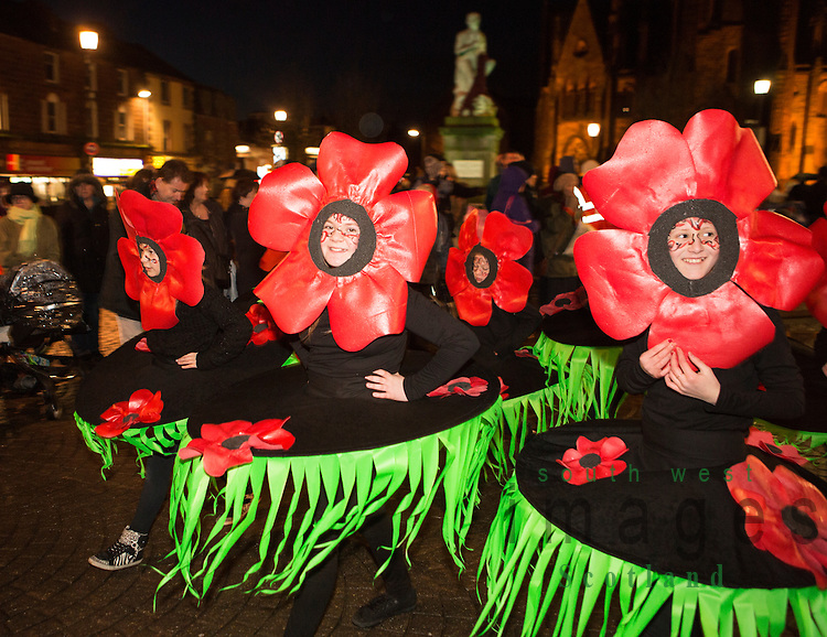 Big Burns Supper 2014, Homecoming Carnival through the streets of Dumfries, Community groups with lanterns and puppets make there way through Dumfries town centre. Kids in fancy dress, poppies, dance through town with Burns Statue behind