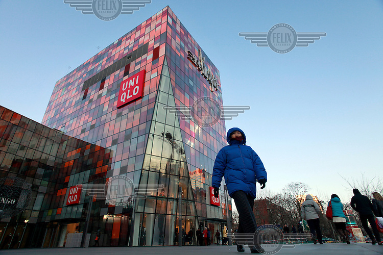 A woman walks near a Uniqlo shop in Sanlitun Village, a shopping centre developed by SOHO China Limited.