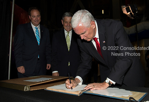 In this photo released by the National Aeronautics and Space Administration (NASA) United States Vice President Mike Pence signs a NASA Kennedy Space Center (KSC) guest book while Acting NASA Administrator, Robert Lightfoot, left, and KSC's director, Robert D. Cabana, center, look on, Thursday, July 6, 2017, in the green room at KSC in Cape Canaveral, Florida. Vice President Mike Pence is scheduled to speak at the event to highlight innovations made in America and tour some of the public/private partnership work that is helping to transform the center into a multi-user spaceport. <br /> Mandatory Credit: Aubrey Gemignani / NASA via CNP