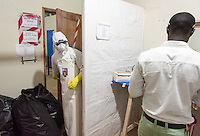"Hygienist Augustine T.J. Bindi enters the ""red zone"" in which suspected and confirmed patients with Ebola are cared for at the ELWA II ETU (Ebola treatment unit) in Monrovia, Liberia on Tuesday, March 3, 2015. Occidental College professor Mary Beth Heffernan's PPE Portrait Project involves creating wearable portraits of health care workers who must wear PPE. <br /> (Photo by Marc Campos, Occidental College Photographer) Mary Beth Heffernan, professor of art and art history at Occidental College, works in Monrovia the capital of Liberia, Africa in 2015. Professor Heffernan was there to work on her PPE (personal protective equipment) Portrait Project, which helps health care workers and patients fighting the Ebola virus disease in West Africa.<br />