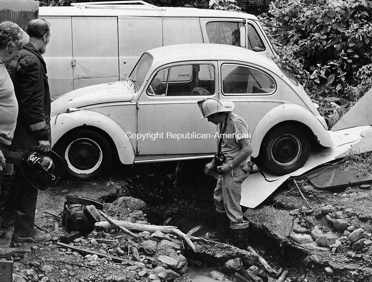 Heavy underground water flow tore out stretches of streets July 14, 1975, including the paved area under this car parked on Depot Street in Watertown. About 30 families were evacuated from their homes.