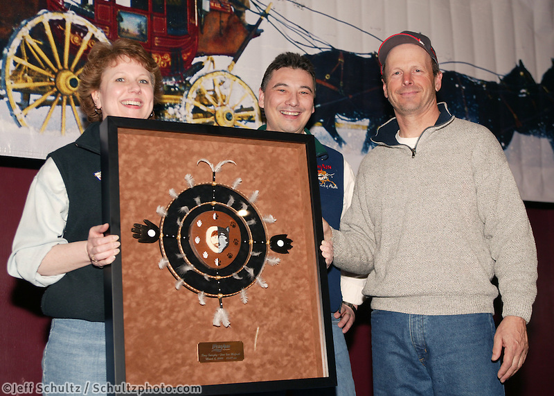 Doug Swingley is presented the PenAir Spirit of Alaska Award for reaching McGrath first.  Re-presenting the award is Danny Seybert, Chief Operating Officer and Patty Daniel, District Sales Manager for PenAir.