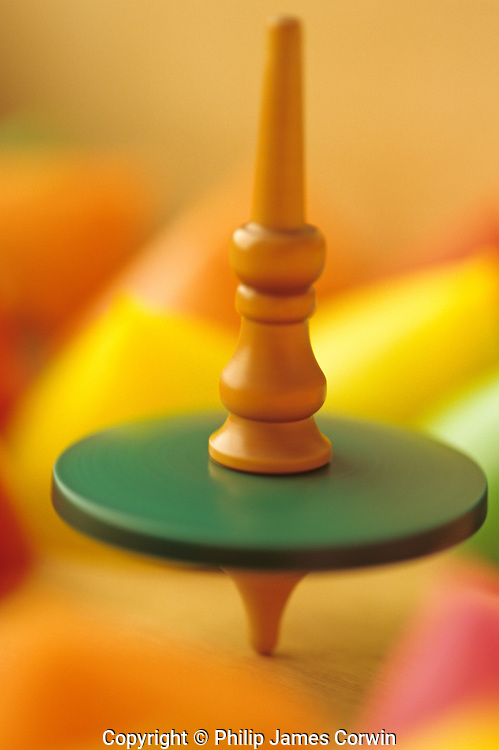 One old wooden spinning top spinning among motionless colorful upside down spinning tops.