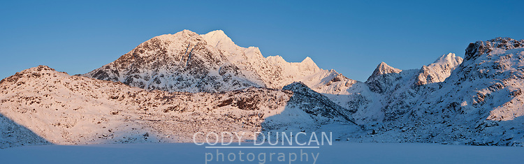 Snow covered mountain peaks of Himmeltindene rise above Vikvatnet lake in winter, Lofoten Islands, Norway