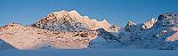 Snow covered mountain peaks of Himmeltindene rise above Vikvatnet lake in winter, Lofoten Islands, Norway
