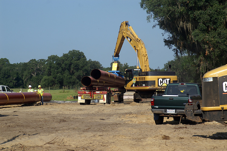 Section of pipe are delivered to the work area by truck.  An electromagnetic head on the arm of a 360 degree excavator is used to unload the pipe and place it on the ground.