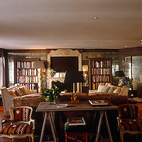 Twin bookcases are framed by antique mirrored tiles with a central flatscreen TV neatly incorporated into the woodwork of the mantelpiece in the drawing room