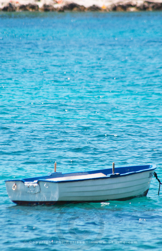 A white and blue rowing boat moored by a white buoy on a bright blue sea. Uvala Sumartin bay between Babin Kuk and Lapad peninsulas. Dubrovnik, new city. Dalmatian Coast, Croatia, Europe.