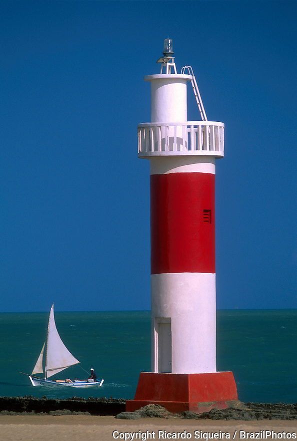 Sailing boat passes near Galinhos lighthouse ( Farol de Galinhos )at Rio Grande do Norte State, northeastern Brazil.