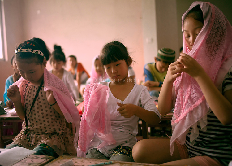 China / Henan Province / Luoyang / Mapo village / 4.7.2013 / Young girls at the Koranic summer school try the new veil they have to wear as a uniform.<br /> &copy; Giulia Marchi