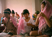 China / Henan Province / Luoyang / Mapo village / 4.7.2013 / Young girls at the Koranic summer school try the new veil they have to wear as a uniform.<br />