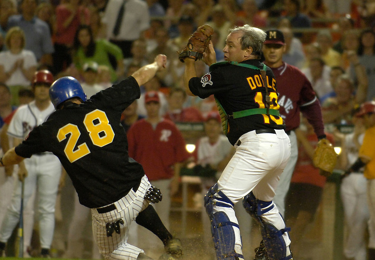 Kenny Hulshof slides into home as Mike Doyle tries in vein to apply the tag during the 44th Annual Roll Call Congressional Baseball Game at RFK Stadium in Washington D.C.