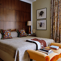 Different shades of brown in the patterns of the soft furnishings complement the wood panelled wall of the bedroom