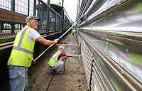 NWA Democrat-Gazette/DAVID GOTTSCHALK Gary Crumley (left) and Anita Taylor, yard conductors, clean Thursday, July 5, 2018, the exterior of the Silver Feather Premium  railcar Arkansas & Missouri Railroad yard in Springdale. The railcar was built in 1948 and currently has table seating in the dome and vestibule ends.
