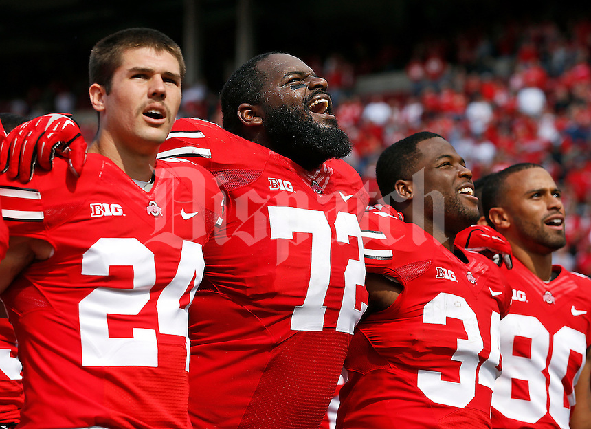 "Ohio State players, from left, kicker Drew Basil (24), defensive lineman Chris Carter (72), running back Carlos Hyde (34) and wide receiver Chris Fields (80), sing ""Carmen Ohio"" following the Buckeyes' 76-0 win over Florida A&M in the NCAA football game at Ohio Stadium in Columbus on Sept. 21, 2013. (Adam Cairns / The Columbus Dispatch)"