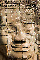 A full frontal view of one of the nearly 200 massive faces carved into the towers and walls of the Bayon, Angkor. This temple, one of the most impressive religious constructions in the world, was started by the Khmer Emperor Jayavarman VII in the early 13th century and some scholars think that the faces are representations of him. Others say that they belong to the boddhisattva of compassion called Avalokitesvara or Lokesvara. At various times in its history, it was a Buddhist and a Hindu temple.