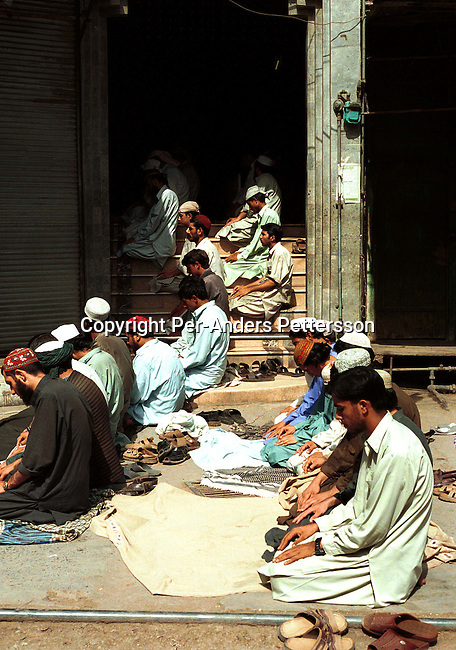 People praying outside a mosque before a pro-Taleban demonstration on September 21, 2001 in the old town in Peshawar, Pakistan. During a national strike people demonstrated all over the country in support of Osama Bin Laden and the Taleban movement in Afghanistan..Photo: Per-Anders Pettersson/ iAfrika Photos...