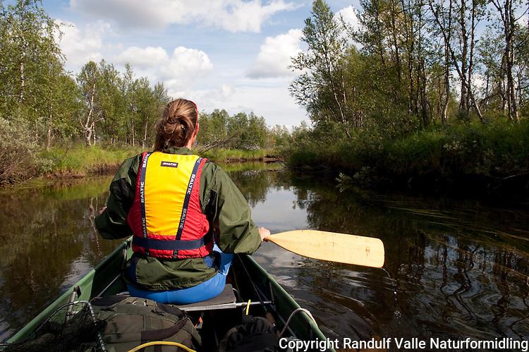 Dame padler kano på liten elv. ---- Woman canoeing on small river.