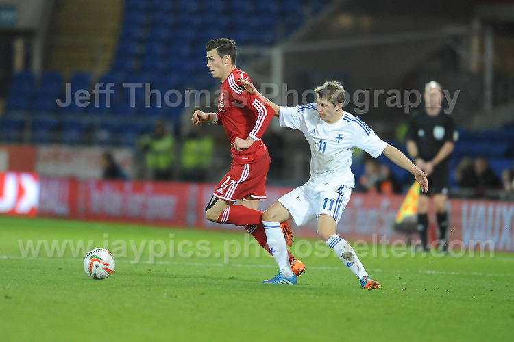 Gareth Bale of Wales keeps procession of the ball despite the challenge of Riku Riski of Finland during the Wales v Finland Vauxhall International friendly football match at the Cardiff City stadium, Cardiff, Wales. Photographer - Jeff Thomas Photography. Mob 07837 386244. All use of pictures are chargeable.