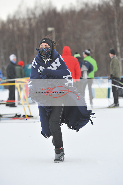 Wrapped up in blankets and scarves, Kestrel Gilliam of Eagle River runs to warm up during the Service Snowball races at a cold and windy Kincaid Park Saturday, Dec. 3, 2016.  Photo by Michael Dinneen for the Star.