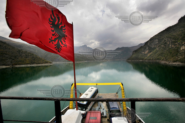 The Albanian national flag flying above the cars on a ferryboat traversing Lake Komani. The ferry, linking Fierze with Bregluma in northern Albania, is the only access to the Tropoja district.