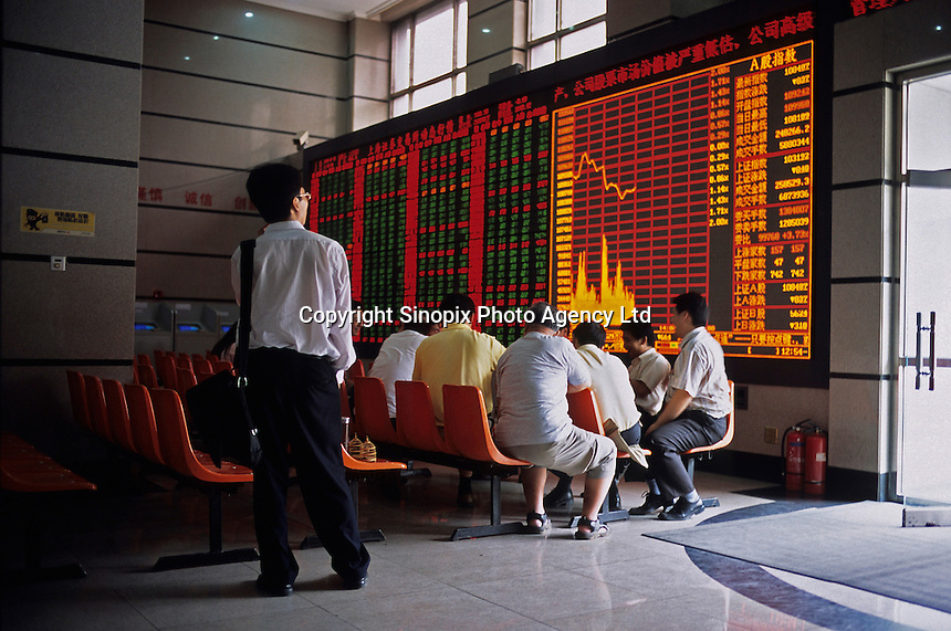 A stock trader watches the board at a stock exchange July, 15, 2005 in Beijing, China. (Lou Linwei/Sinopix)