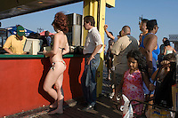 A woman in a bikini waits in line for a hotdog at Nathan's. Street photography in Coney Island, Brooklyn,  NY August 4, 2007