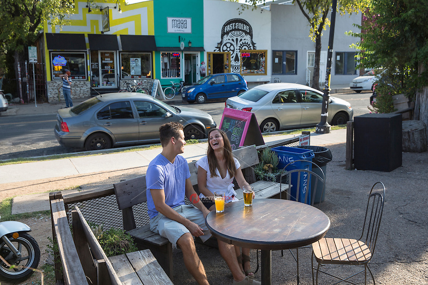 Young couple enjoy drinking beer at outdoor patio bar on East 6th Street, in East Austin, Texas.