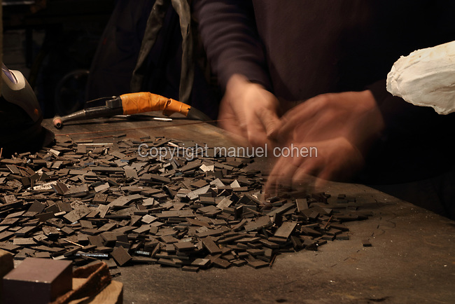 Nicolas Desbons, metalworker and artist, selecting squares of steel for a figurative sculpture made by placing steel pieces inside a plaster mould and soldering them together, in his Soleil Rouge workshop, photographed in 2017, in Montreuil, a suburb of Paris, France. Desbons works mainly in steel but often in conjunction with other materials such as fibreglass, glass and clay, using both cold metal and forge techniques. He produces both figurative and abstract sculptures as well as furniture and lighting. Picture by Manuel Cohen
