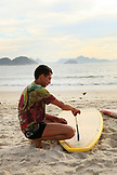 BRAZIL, Rio de Janiero, a man fixing the fin of his surboard on Copacabana Beach