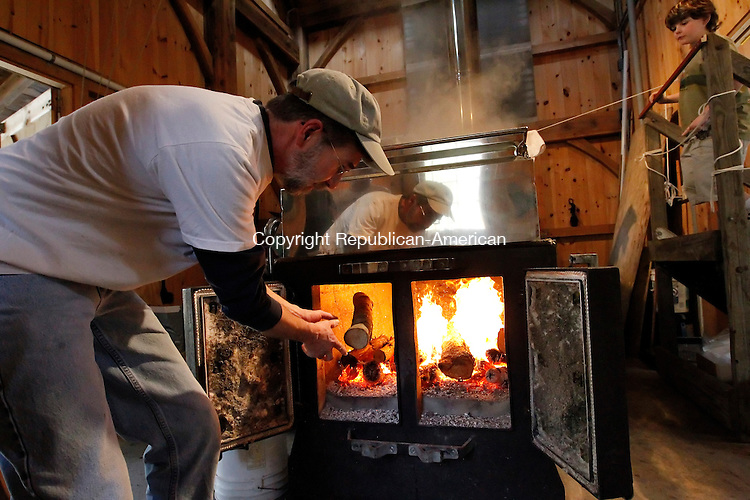 Woodbury, CT-20, March 2010-032010CM02 COUNTRY LIFE USE ONLY  Harry Gerowe, a volunteer at Flander's Nature Center in Woodbury, throws logs into the evaporator, which boils down sap to get to the concentration of syrup, Saturday afternoon.  He was helping out during the annual Maple Celebration.  Looking on is Maxwell Bartlett, 9 of Seymour.        --Christopher Massa Republican-American