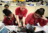 NWA Democrat-Gazette/DAVID GOTTSCHALK  Robert Saunders, assistant department head of Electrical Engineering at the University of Arkansas, helps test Wednesday, June 14, 2017, the soldered components of a circuit board with Dyani Hogan (from left), of Roberta, GA., Erin Searcy, Stone Mountain, GA., and Ira-Maria Onate while participating in the seven day Math, Science, Engineering Academy on the campus in Fayetteville. The high school age students were building a solar paneled cell phone charger. The camp emphasizes the science, technology, engineering and mathematics fields.