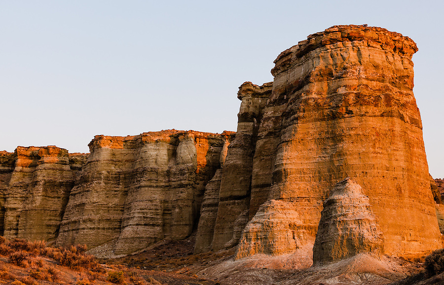The warm light of sunrise casts light on the sides of one of the sandstone formations at the Pillars of Rome in Southeast Oregon.