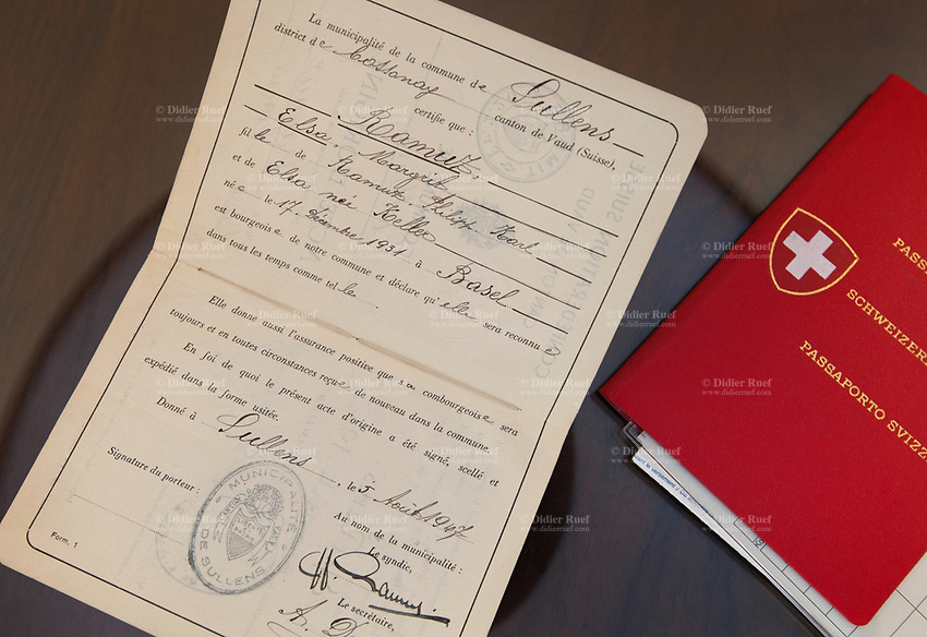 """Switzerland. Canton Ticino. Sala. A booklet with the place of origin and swiss passport laid on a table in the living room of Elsy (Elsa) Hofer Ferrari Ramuz . In Switzerland, the place of origin (German: Heimatort or Bürgerort, literally """"home place"""" or """"citizen place""""; French: Lieu d'origine; Italian: Luogo d'origine) denotes where the Swiss citizen has his municipal citizenship. It is not to be confused with the place of birth or the place of residence, although two or all three of these locations can be identical depending on the person. The front cover of a Swiss passport. The passport is issued to citizens of Switzerland to facilitate international travels. The flag of Switzerland consists of a red flag with a white cross (a bold, equilateral cross) in the centre. It is one of only two square sovereign-state flags. Elsy Hofer Ferrari Ramuz is the niece of Charles-Ferdinand Ramuz (September 24, 1878 – May 23, 1947) who was a French-speaking Swiss writer.  14.11.2017 © 2017 Didier Ruef"""