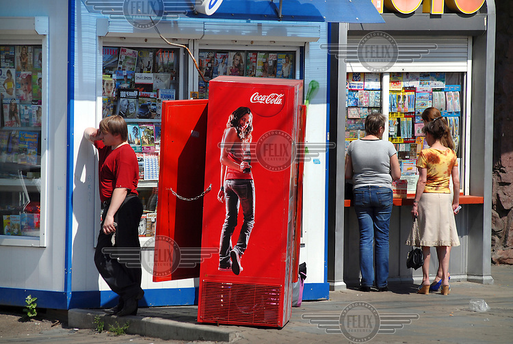 A man talks on a mobile phone near an advert for Coca Cola outside a shop in the city centre of Krasnoyarsk.