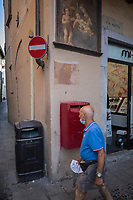 Italy. Lombardy Region. Como. Town center. An elderly man wears on his neck a mask against Coronavirus ( also called Covid-19). A shops sells make up accessories for women. On the wall, a religious painting about the Virgin Mary holding her son jesus Christ in her arms. A red letter box from the Italian Post service. A no-entry traffic sign. Como is a city and comune. It is the administrative capital of the Province of Como. 8.07.2020  © 2020 Didier Ruef
