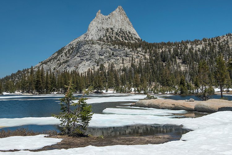 In Yosemite's high country, Upper Cathedral Lake, situated at an elevation of 9585 feet, retains its frozen lake surface well into springtime.