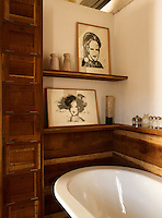 A pair of pen and ink drawings on shelves in the wood panelled bathroom