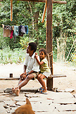 PHILIPPINES, Palawan, Barangay region, a Batak father and his daughter sit in front of their home in Kalakwasan Village