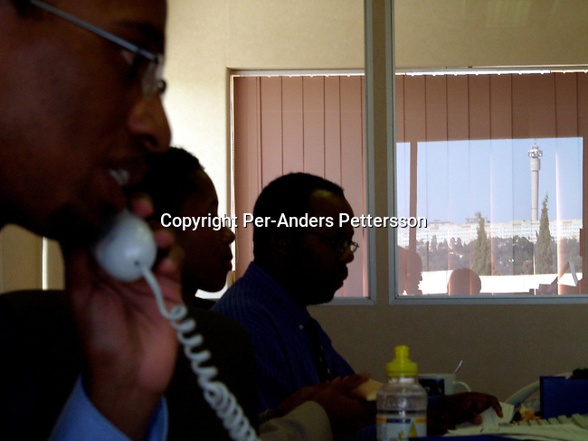 dibucor00035 Business Corporate.  Andile Mazwai, a young black successful businessman and the only black stockbroker in South Africa working in his office on Junel 10, 2002 in Johannesburg, South Africa. Black empowerment. Telephone, office, black business men.©Per-Anders Pettersson/iAfrika Photos.