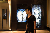 A Chinese man walks past a shop selling luxury watches in a shopping centre in Central Macau, China.