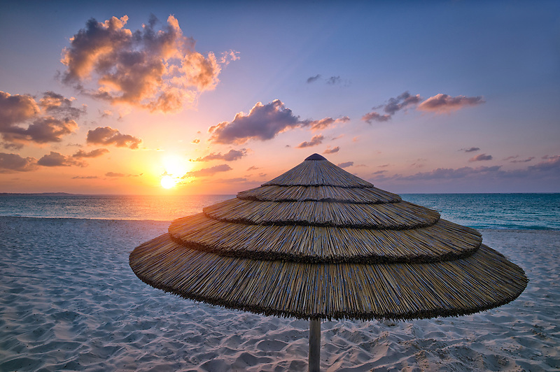 Reed umbrella and sunset. Grace Bay. Providenciales. Turks and Caicos.