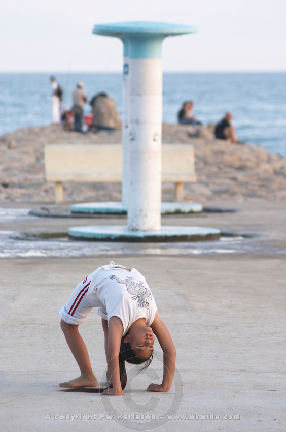 A young girl doing gymnastics bending back on the beach pier. Sitges, Catalonia, Spain